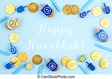 Blue background with dreidels, menora candles and chocolate coins with Happy Hanukkah wording