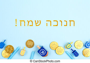 Blue background with multicolor dreidels, menora candles and chocolate coins with Happy Hanukkah wording in Hebrew