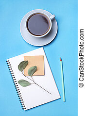 Blue background with notepad, pencil and cup of coffee.