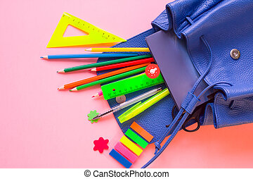 Blue backpack with school supplies on pink background....