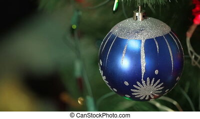 blue ball with garland on a Christmas tree