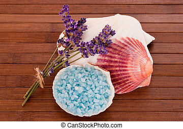 Blue bath salts with lavender blossoms over wooden background