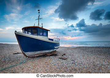Blue BBoat on a Shingle Beach - A blue fishing boat hight up...