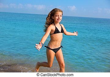 blue beach kid girl with bikini jumping and running splashing water