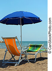 blue beach umbrella and two deckchairs on the beach
