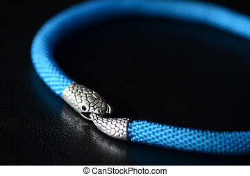 Blue beaded necklace with snake head lock on a dark background close up