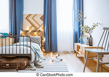 Blue curtain and wooden board behind bed with lights in bedroom interior with grey chair and plants