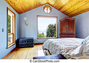 Blue bedroom with wood ceiling and bed, large windows interior