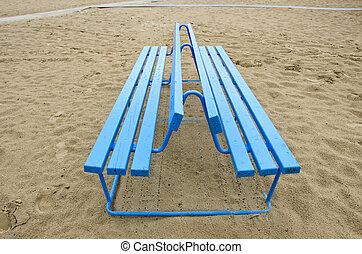 blue bench on sea beach sand
