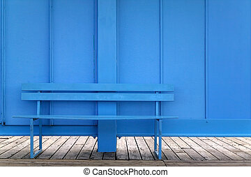 Blue bench against a blue wall.