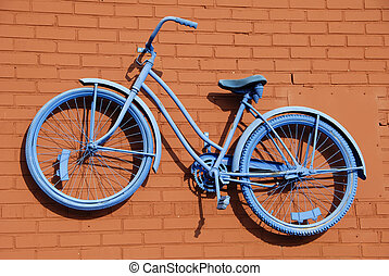 Antique bicycle painted blue and mounted to a rust colored brick wall
