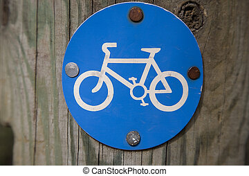 Blue Bicycle Sign on Wooden Post