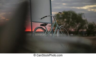 Blue bicycle stays at the signboard on a beach in summer sunset. Pan horizontal.