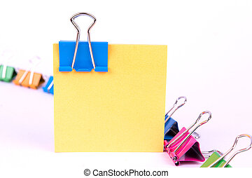 Blue binder clip on yellow paper note