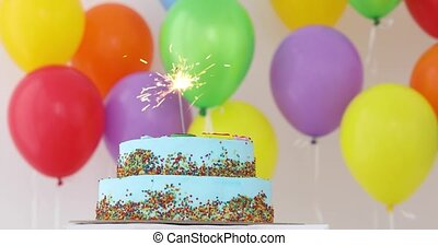 Blue Birthday cake with sparkler and colorful balloons