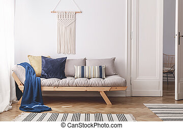 Blue blanket and pillows on grey wooden couch in white living room interior with door. Real photo