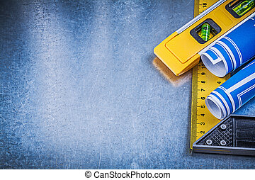 Blue blueprints construction level square ruler on metallic background.
