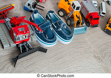 Blue boat shoes for boy near set of car toy on grey wooden background. Top view. Frame. Copy space.