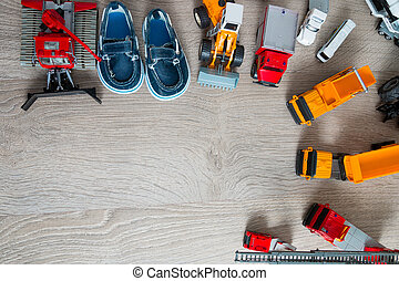 Blue boat shoes for boy near set of car toy. Top view. Frame. Copy space.