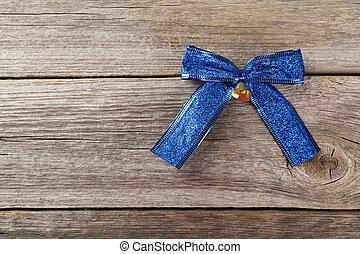 Blue bow on grey wooden background