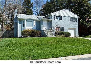 Blue brick split-level single family house in suburban Maryland.  Nice Lawn
