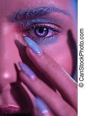 Blue bright eyes of a stylish girl model with hands near the face in the frame.