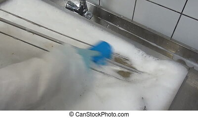 Blue brush in hand of worker cleans industrial meat grill....