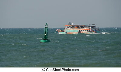 Blue buoy in the sea is sailing by a passenger ferry - A...