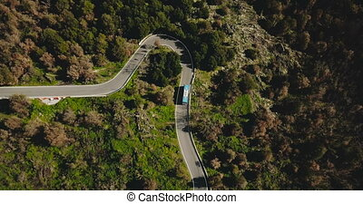 Blue bus turns left on a mountain road aerial view....