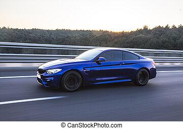 Blue business class sedan on the road