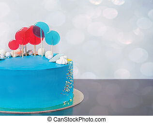 Blue buttercream Birthday cake with colorful lollipops.