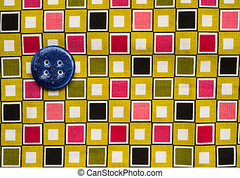 blue button on colourful fabric