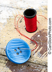 Blue button with needle and thread