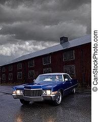 Blue cadillac with a male driver on a rainy day