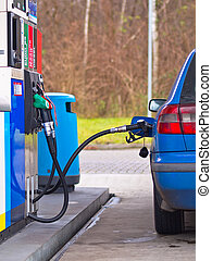 Blue car at gas station being filled with fuel against...