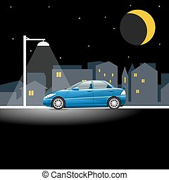 Blue car on an empty city street at night