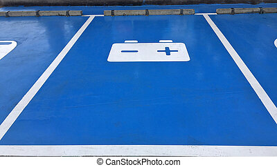 Blue car park and white symbolic of battery on the floor, ...
