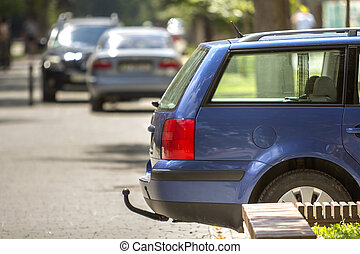Blue car parked on sunny street, red stop lights, hook for dragging trailer, tow hitch or towbar.