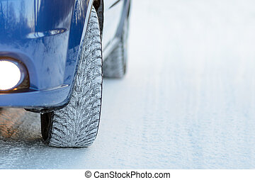 Blue Car with Winter Tires on the Snowy Road. Drive Safe.