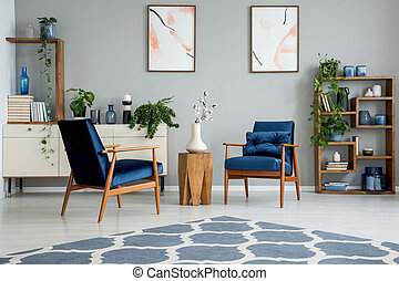 Blue carpet in grey living room interior with posters and wooden table between armchairs. Real photo
