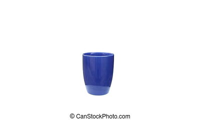 blue ceramic cup rotating on isolated white
