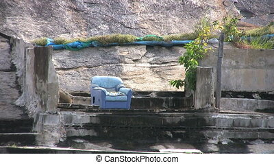 Blue Chair On A Rock - A blue chair sits precariously on the...