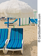 blue chairs at beach with umbrella