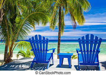 Blue chairs on a beach front on amazing beach - Two blue ...