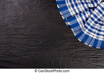 blue checkered tablecloth on the black stone table with copy space for your text. Top view