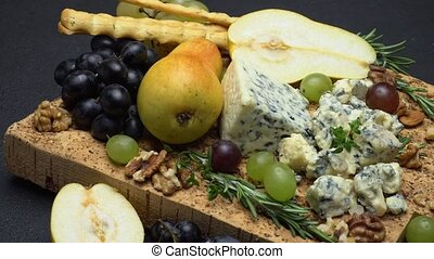 blue cheese and fruits on cork wooden serving board - dark...
