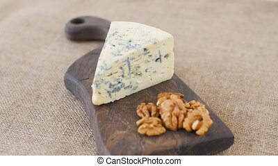 Blue cheese and nuts rotate on a wooden serving board