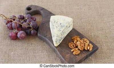 Blue cheese and nuts rotate on a wooden serving board - Blue...