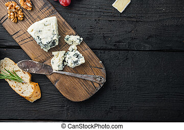 Blue cheese Gorgonzola, on black wooden table, flat lay with copy space for text