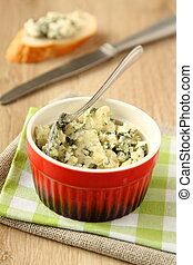 Blue cheese in red bowl on wooden background